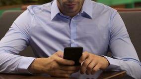 Στοχαστικό αρσενικό που τυλίγει την κινητή τηλεφωνική οθόνη, κοινωνικά μέσα, απογοήτευση φιλμ μικρού μήκους