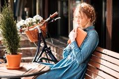 Στοχαστικό βιβλίο γυναικών readng και να ονειρευτεί στο beanch υπαίθρια στοκ φωτογραφία με δικαίωμα ελεύθερης χρήσης