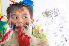 Στοχαστικό δημιουργικό μικρό παιδί που καλύπτεται στο χρώμα στοκ εικόνα