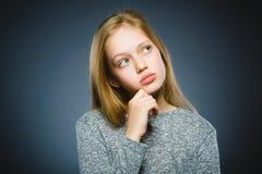 Στοχαστικό κορίτσι κινηματογραφήσεων σε πρώτο πλάνο με το χέρι στο κεφάλι που απομονώνεται σε γκρίζο Στοκ Φωτογραφία