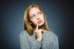 Στοχαστικό κορίτσι κινηματογραφήσεων σε πρώτο πλάνο με το χέρι στο κεφάλι που απομονώνεται σε γκρίζο Στοκ Εικόνες