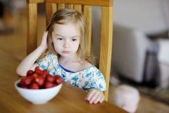 Στοχαστικό κορίτσι με τις φρέσκες φράουλες σε ένα κύπελλο στοκ εικόνες
