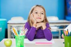 Στοχαστικό κορίτσι με το χέρι στη συνεδρίαση πηγουνιών στο γραφείο Στοκ Φωτογραφίες