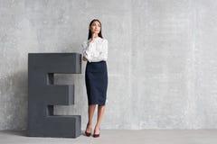 Στοχαστικό κορίτσι που στέκεται κοντά στην τεράστια επιστολή Στοκ Εικόνες