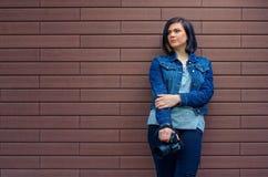 Στοχαστικό κορίτσι σε ένα σακάκι τζιν παντελόνι με τη ψηφιακή κάμερα Στοκ φωτογραφία με δικαίωμα ελεύθερης χρήσης