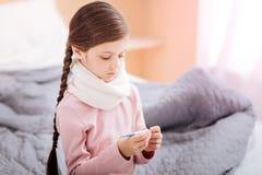 Στοχαστικό κορίτσι στα θερμά ενδύματα που κρατά ένα θερμόμετρο Στοκ φωτογραφία με δικαίωμα ελεύθερης χρήσης