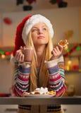 Στοχαστικό κορίτσι στο καπέλο santa με το μπισκότο Στοκ εικόνα με δικαίωμα ελεύθερης χρήσης
