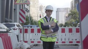 Στοχαστικό μικρό παιδί που φορούν τον εξοπλισμό ασφάλειας και σχέδιο οικοδόμησης εκμετάλλευσης κρανών κατασκευαστών που στέκεται  απόθεμα βίντεο