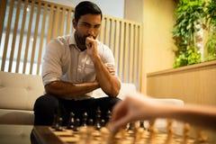 Στοχαστικό σκάκι παιχνιδιού επιχειρηματιών με τη γυναίκα συνάδελφος Στοκ εικόνα με δικαίωμα ελεύθερης χρήσης