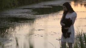 Στοχαστικό Brunette στο άσπρο φόρεμα που υπερασπίζεται τον ποταμό στους καλάμους με τον κόκκορα παραδίδει επάνω το χρόνο του ηλιο φιλμ μικρού μήκους