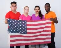 Στούντιο που πυροβολείται της διαφορετικής ομάδας πολυ εθνικών φίλων που κρατούν στοκ εικόνες