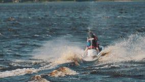 Στο άτομο τη φανέλλα ζωής και αγόρι στο κράνος και η πορτοκαλιά φανέλλα οδηγούν ένα αεριωθούμενο σκι στην ταχύτητα ύψους φιλμ μικρού μήκους