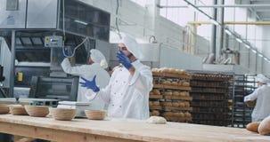 Στο αρτοποιείο ένας ευτυχής χορεύοντας αρτοποιός βιομηχανίας έχει έναν χρόνο διασκέδασης προετοιμάζοντας τη ζύμη για την κατασκευ φιλμ μικρού μήκους