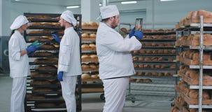 Στο αρτοποιείο ένας κύριος αρτοποιός βιομηχανίας με μια νέα ταμπλέτα παίρνει μερικές εικόνες του φρέσκου ψημένου ψωμιού άλλοι δύο φιλμ μικρού μήκους