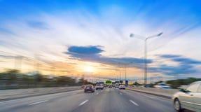 Στο δρόμο στην ελαφριά κυκλοφορία εθνικών οδών με το ηλιοβασίλεμα στον αυτοκινητόδρομο Στοκ φωτογραφίες με δικαίωμα ελεύθερης χρήσης