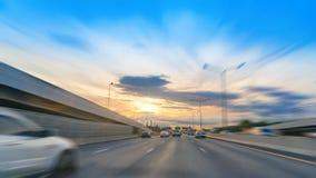 Στο δρόμο στην ελαφριά κυκλοφορία εθνικών οδών με το ηλιοβασίλεμα στον αυτοκινητόδρομο Στοκ εικόνα με δικαίωμα ελεύθερης χρήσης