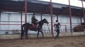 Στο ειδικό υπόστεγο, ένα με ειδικές ανάγκες νεολαίες άτομο μαθαίνει να οδηγά ένα άλογο με το στενό δάσκαλο επίβλεψης, hippotherap φιλμ μικρού μήκους