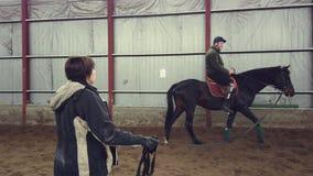 Στο ειδικό υπόστεγο, ένα με ειδικές ανάγκες νεολαίες άτομο μαθαίνει να οδηγά ένα άλογο με το στενό δάσκαλο επίβλεψης, hippotherap απόθεμα βίντεο