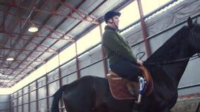 Στο ειδικό υπόστεγο, ένα με ειδικές ανάγκες νεολαίες άτομο μαθαίνει να οδηγά ένα μαύρο, thoroughbred άλογο, hippotherapy το άτομο φιλμ μικρού μήκους