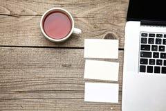 Στο εκλεκτής ποιότητας επιτραπέζιες τσάι, το lap-top και τις επαγγελματικές κάρτες Στοκ φωτογραφία με δικαίωμα ελεύθερης χρήσης