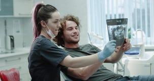 Στο ελαφρύ οδοντικό δωμάτιο μια νέα γυναίκα οδοντιάτρων εξηγεί το αποτέλεσμα της ακτίνας X δοντιών στον ασθενή που έχουν έναν φιλ φιλμ μικρού μήκους