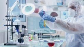 Στο επαγγελματικό σύγχρονο εργαστήριο υψηλών σημείων ο επιστήμονας εξετάζει μερικά δείγματα του υγρού απόθεμα βίντεο