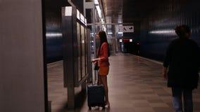 Στο επαγγελματικό ταξίδι Ένας θηλυκός ηγέτης περιμένει το τραίνο της και κοιτάζει στο χρονοδιάγραμμα απόθεμα βίντεο