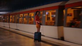 Στο επαγγελματικό ταξίδι - μια νέα σύγχρονη γυναίκα με μια βαλίτσα παίρνει το τραίνο της απόθεμα βίντεο