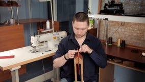 Στο εργαστήριο, ένα άτομο ράβει τα κομμάτια προς κατεργασία δέρματος, κατασκευάζοντας ένα πορτοφόλι απόθεμα βίντεο