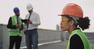 Στο εργοτάξιο οικοδομής που σκέφτεται το νέο αφρικανικό μηχανικό γυναικών στη στέγη της οικοδόμησης φορώντας ένα πορτοκαλί κράνος απόθεμα βίντεο