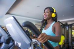 Στο εσωτερικό πορτρέτο γυμναστικής της νέας ελκυστικής και ευτυχούς αμερικανικής γυναίκας μαύρων Αφρικανών με τα ακουστικά που εκ στοκ φωτογραφία με δικαίωμα ελεύθερης χρήσης