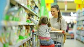 Στο εσωτερικό πορτρέτο νέου ελκυστικού Mom και λίγων τροφίμων αγοράς παιδιών σε μια υπεραγορά Πλάγια όψη της ευτυχούς οικογένειας απόθεμα βίντεο