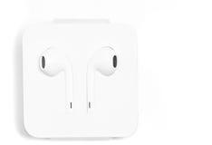 Στο λευκό ακουστικών αυτιών σε ειδική περίπτωση από τη Apple με το lightnin Στοκ Εικόνες