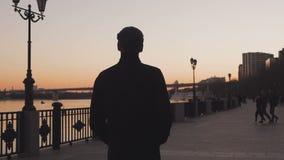 Στο ηλιοβασίλεμα, στο σούρουπο, ένας νεαρός άνδρας σε ένα παλτό περπατά κατά μήκος ενός πεζοδρομίου κατά μήκος ενός ποταμού πίσω  φιλμ μικρού μήκους