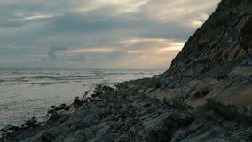 Στο ηλιοβασίλεμα τα κύματα καταβρέχουν ήπια για τη δύσκολη ακτή απόθεμα βίντεο
