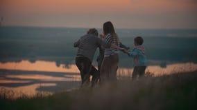 Στο ηλιοβασίλεμα, τα χέρια οικογενειακής λαβής, έχουν τη διασκέδαση που χορεύει και που περιστρέφει απόθεμα βίντεο