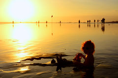 Στο ηλιοβασίλεμα το αστείο μωρό παραλιών κάθεται στη μαύρη υγρή άμμο και το σύρσιμο στην κυματωγή θάλασσας για την κολύμβηση στα  Στοκ Φωτογραφία
