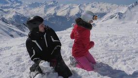 Στο θέρετρο βουνών ένα εύθυμο ζευγάρι των σκιέρ που παίζουν τις χιονιές απόθεμα βίντεο