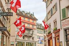 Στο κέντρο της πόλης, παλαιά οδός της Ζυρίχης με τις ελβετικές σημαίες Στοκ φωτογραφία με δικαίωμα ελεύθερης χρήσης