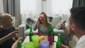 Στο καθιστικό οι φίλοι που παίζουν το cWho είναι παιχνίδι Ι με τα κολλώδη έγγραφα για το κεφάλι απόθεμα βίντεο