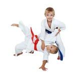 Στο κιμονό το αγόρι ρίχνει ένα κορίτσι σε ένα κιμονό που απομονώνεται Στοκ Εικόνες