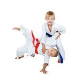 Στο κιμονό το αγόρι ρίχνει ένα κορίτσι σε ένα κιμονό που απομονώνεται Στοκ Φωτογραφία