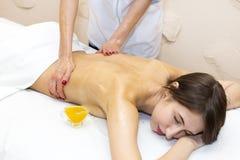 Στο κορίτσι δίνεται ένα θεραπευτικό μασάζ με το μέλι μελισσών Στοκ Εικόνες