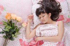 Στο κρεβάτι δίπλα στον ύπνο το νέο κορίτσι βάζει τα λουλούδια στοκ εικόνα