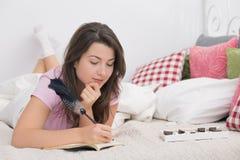 Στο κρεβάτι με το ημερολόγιο στοκ φωτογραφίες με δικαίωμα ελεύθερης χρήσης