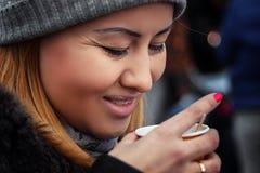 Στο κρύο καιρό, μια όμορφη νέα γυναίκα σε μια ΚΑΠ πίνει το καυτό τσάι από ένα φλυτζάνι πλαστικών στοκ φωτογραφία