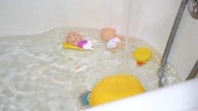 Στο λουτρό με τα παιχνίδια των παιδιών το καθαρό νερό προέρχεται από τη βρύση για να λούσει το μωρό απόθεμα βίντεο
