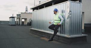 Στο μέσο της ημέρας εργασίας σε έναν χαμογελώντας αρχιτέκτονα εργοτάξιων οικοδομής που απολαμβάνει το χρόνο σπασιμάτων αυτός που  φιλμ μικρού μήκους