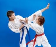 Στο μικρούς πόδι λακτίσματος τραίνων αθλητών karategi και το βραχίονα διατρήσεων Στοκ φωτογραφία με δικαίωμα ελεύθερης χρήσης
