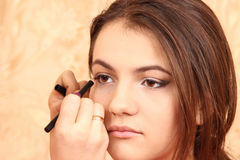 Στο νέο κορίτσι αποτελέστε τα μάτια, βάζει τα καλλυντικά Στοκ Φωτογραφία